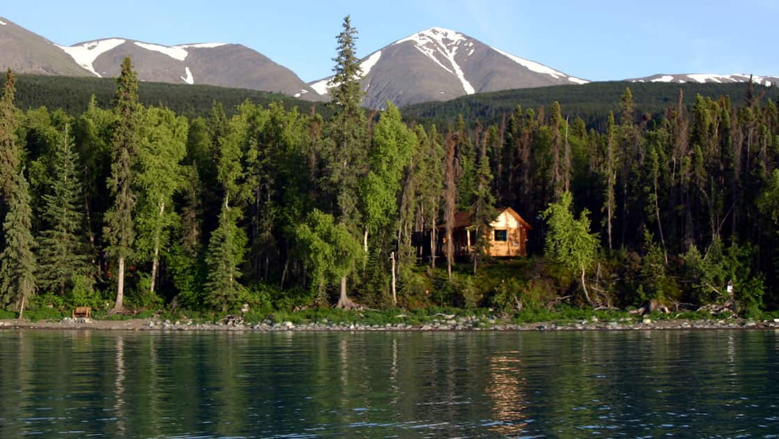 One of the cabins at the Kenai Backcountry Lodge in Alaska is just barely visible through dense forest under mountains and beyond the lake