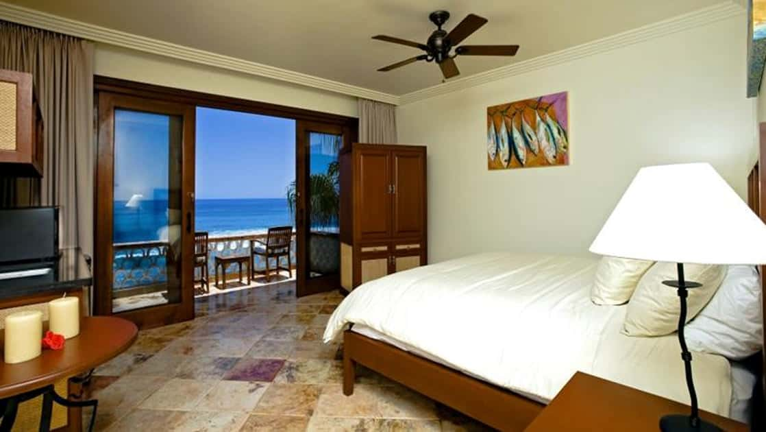 Modern, comfortable, beachfront rooms at the Cabo Surf Hotel in Baja California have comforters, marble floors, and cedar carpentry