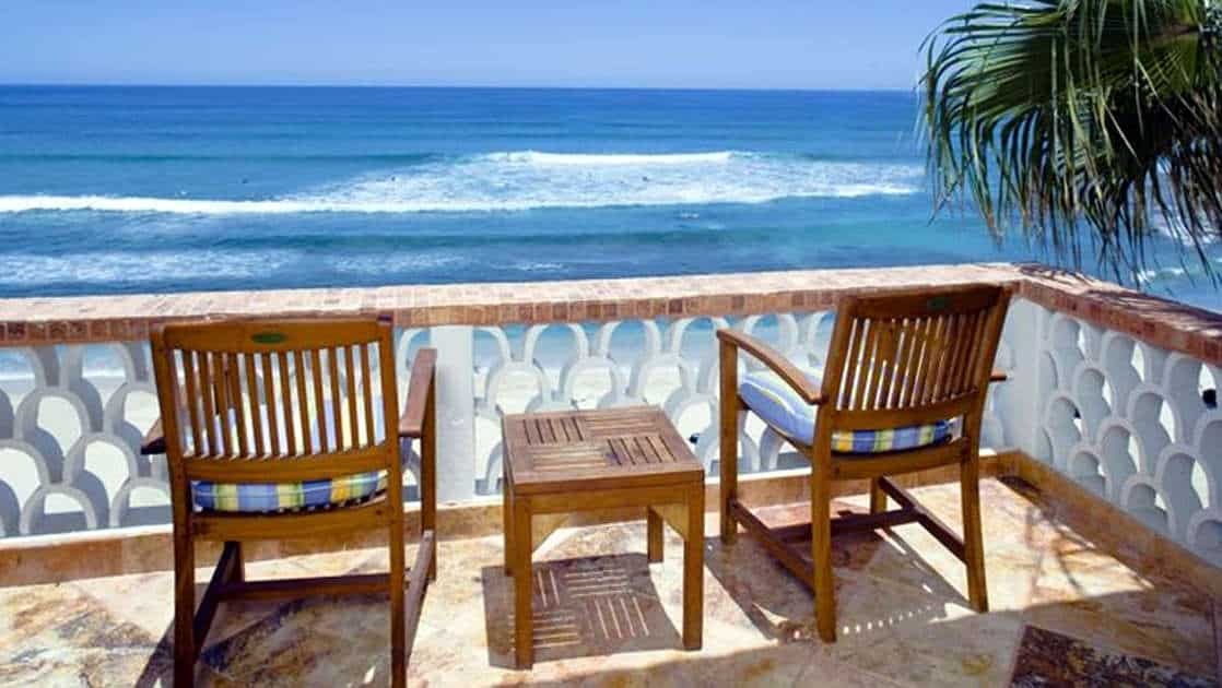 Two chairs and a table on a sunny balcony overlooking the ocean in Baja California, Mexico, at the Cabo Surf Hotel and Spa