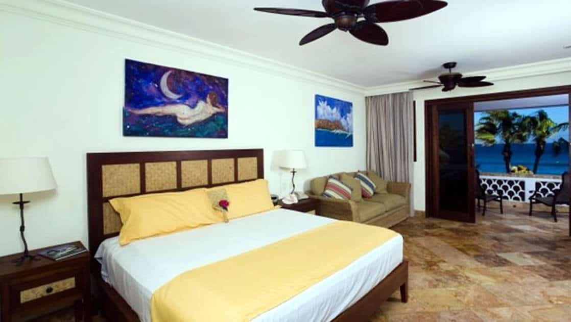 A queen-sized bed in a room with a ceiling fan, art, and marble floors at the Cabo Surf Hotel in Baja California