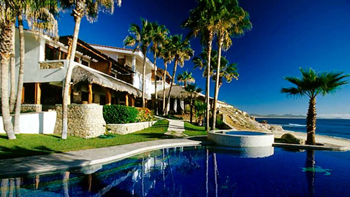 The Cabo Surf Hotel is a boutique beach resort with white stucco walls, surrounded by palm trees, with ocean views in Costa Rica