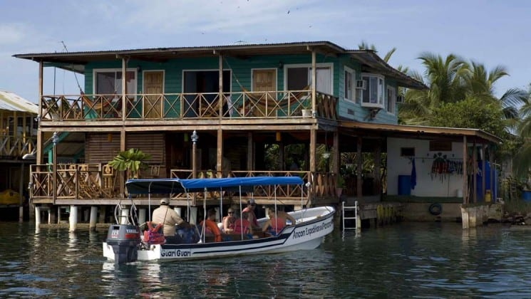 A boat full of people drives toward the Bocas Inn, situated on the water's edge, a family lodge in Bocas del Toro Panama