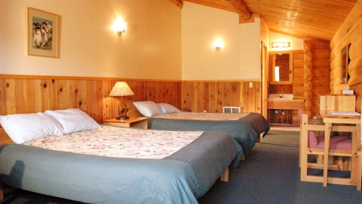 A room with two queen-sized beds at the Kantishna Roadhouse. Down comforters and warm quilts will keep guests warm and cozy on chilly Alaskan summer nights.