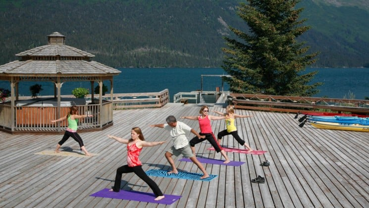 Guests take a yoga class outside on the deck with trees and water in the distance at the Tutka Bay Wilderness Lodge near Homer, Alaska