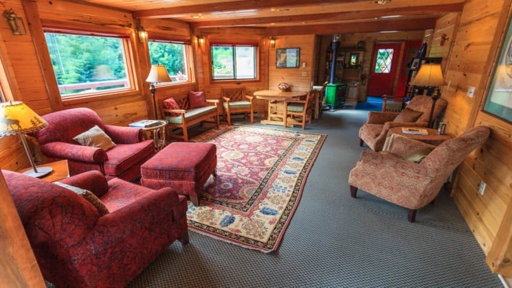 The lounge, with a wood interior, big and comfortable chairs, a rug, and cozy decor, at the Tutka Bay Wilderness Lodge in Alaska