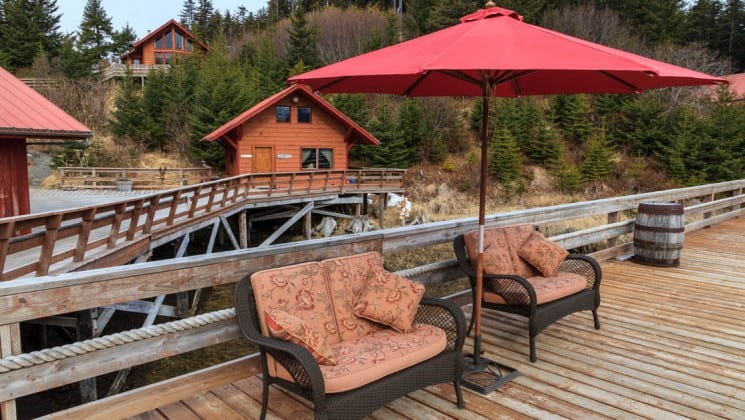 An umbrella is positioned over two chairs on the deck, with boardwalks and cabins in the background, at the Tutka Bay Wilderness Lodge in Alaska
