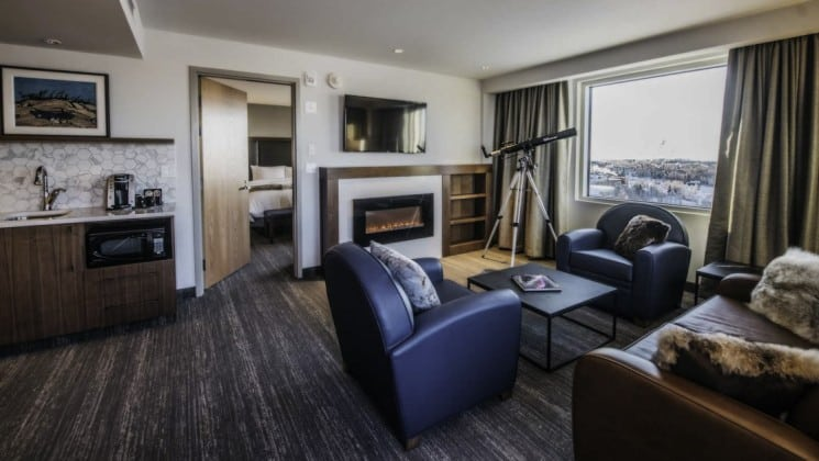 Loveseat, fireplace, two armchairs, coffee table, kitchenette and telescope in Aurora Signature Suite at Explorer Hotel in Yellowknife, Northwest Territories