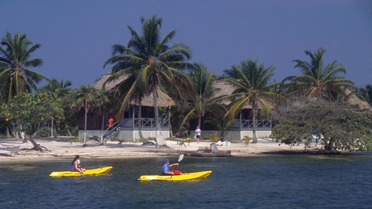 Two kayakers paddle in the ocean, in front of the pristine beach, where the Blackbird Caye Resort in Belize is located