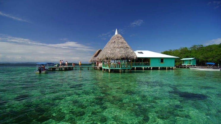 A thatch-roof hut is built on the edge of clear tropical water at Bocas Inn, in Panama