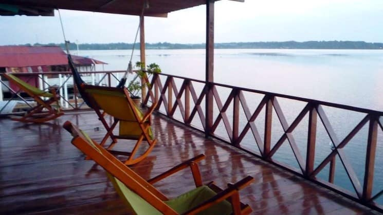 Chairs on a covered, open-air porch face the railing and the water at Bocas Inn at Bocas del Toro in Panama