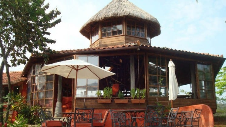 "One of the private bungalows at the Cala Mia Boutique Hotel with a thatched roof, outdoor ""rancho"" patio, hammocks, umbrellas, and handcrafted furniture"