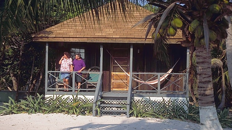 The balcony of a beach-front cabana at the Blackbird Caye Resort in Belize has a hammock strung up. Two people stand on the balcony and look toward the ocean.