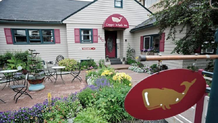 Exterior of Copper Whale Inn in Anchorage, Alaska with red sign with a painted copper whale