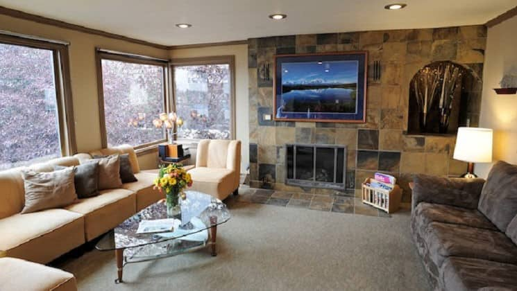 Large living room with two couches, art on walls and large windows at Copper Whale Inn in Anchorage, Alaska