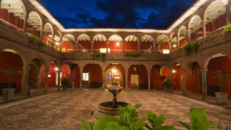 Large outdoor courtyard with small fountain centerpiece and several plants at Costa del Sol Ramada Cusco in Peru