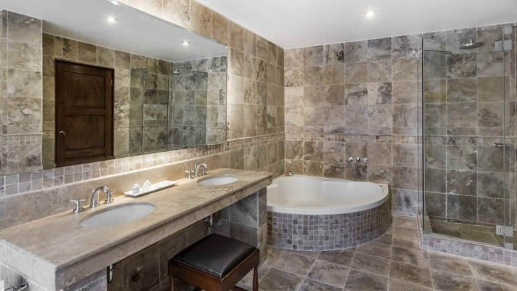 Tiled bathroom with glass enclosed shower, soaking tub, large mirror and two sinks at Costa del Sol Ramada Cusco in Peru