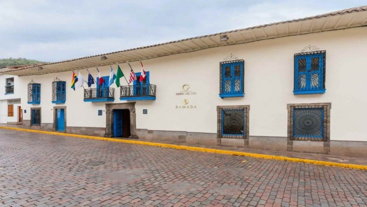 Exterior of Costa del Sol Ramada Cusco in Peru with international flags hanging above main entrance