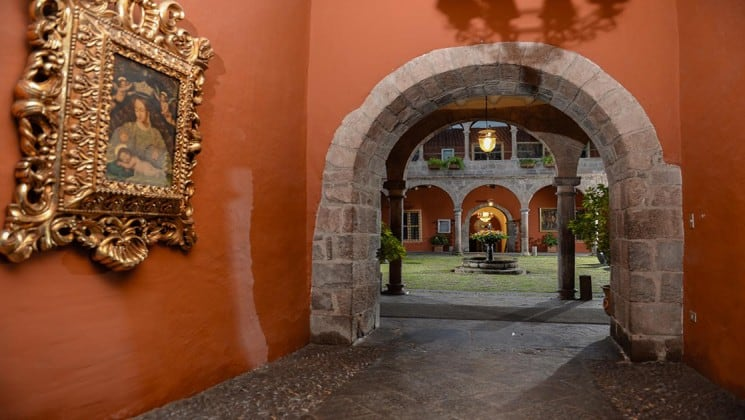 Walkway leading to outdoor courtyard, with gilded framed art on wall at Costa del Sol Ramada Cusco in Peru