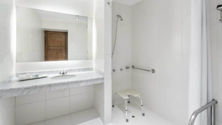 ADA compliant shower with seat and support bars next to sink in bathroom at Peru's Costa del Sol Ramada Cusco