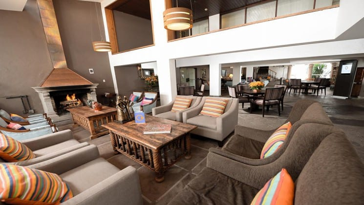 Lobby area with fireplace, multiple tables and several oversize chairs at Costa del Sol Ramada Cusco on Peru