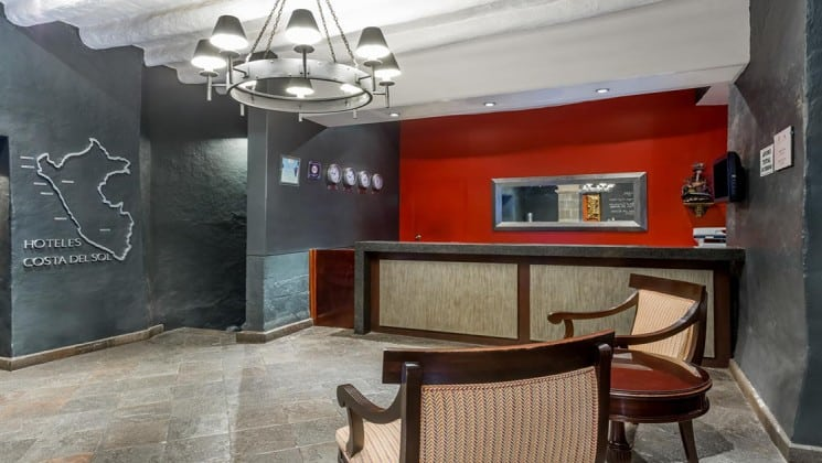 Lobby with reception desk, two seats, and large image of Peru at Costa del Sol Ramada Cusco