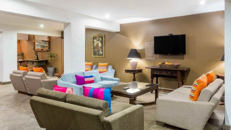 Hotel lobby with five loveseats, coffee table and TV on wall at Costa del Sol Ramada Cusco in Peru