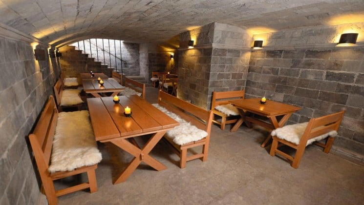 The basement pub with long wooden tables with a candle in the middle, and wooden benches covered in soft wool at Costa del Sol Ramada Cusco in Peru