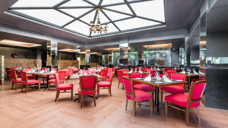 Spacious restaurant with many tables, each set with four chairs, at Costa del Sol Ramada Cusco in Peru