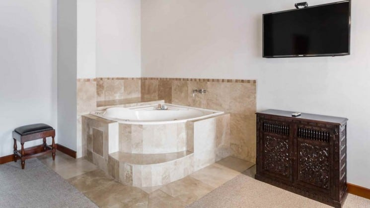 Jacuzzi with fine tiling, with TV hanging on wall nearby in suite at Costa del Sol Ramada Cusco in Peru