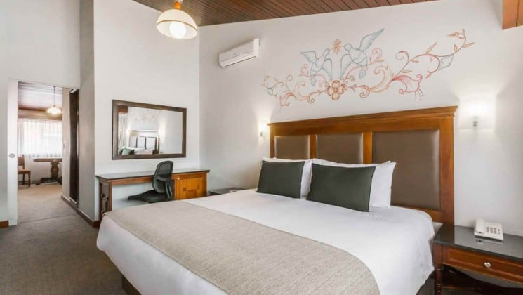 King bed with hand-painted birds on wall, small writing desk and bedside table in king suite at Costa del Sol Ramada Cusco in Peru