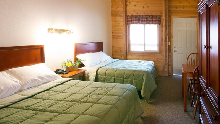 Two queen-sized beds with green down comforters inside one of the guest cabins at Kantishna Roadhouse, an Alaskan lodge in Denali National Park