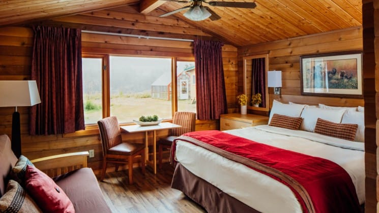 King bed, windowside table and two chairs, wooden detailing and futon in Superior Cabin at Denali Backcountry Lodge in Kantishna, Alaska