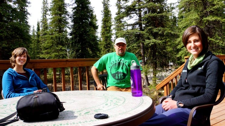 Three people sit around a table on a wooden porch surrounded by trees at Denali Education Center near Denali National Park in Alaska