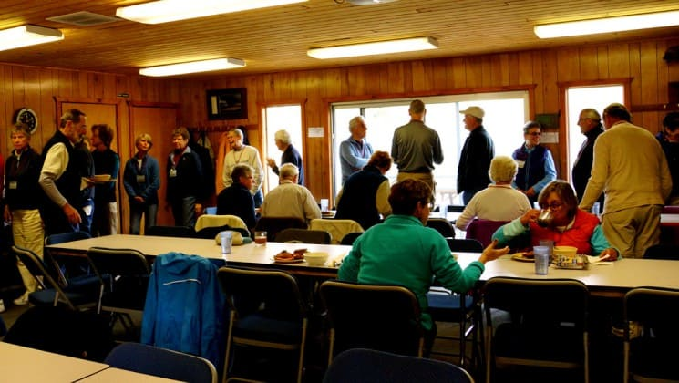More than 20 people sit at tables or stand in line for food in the dining hall at Denali Education Center in Alaska
