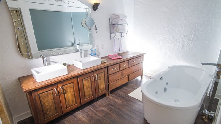 Bathroom with large soaking tub, two sinks and large mirror at El Mercado Tunqui in Cusco, Peru
