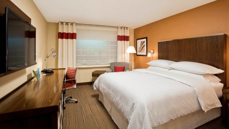 Room with king bed, desk, armchair, table, window, mounted TV at Four Points by Sheraton in Juneau, Alaska