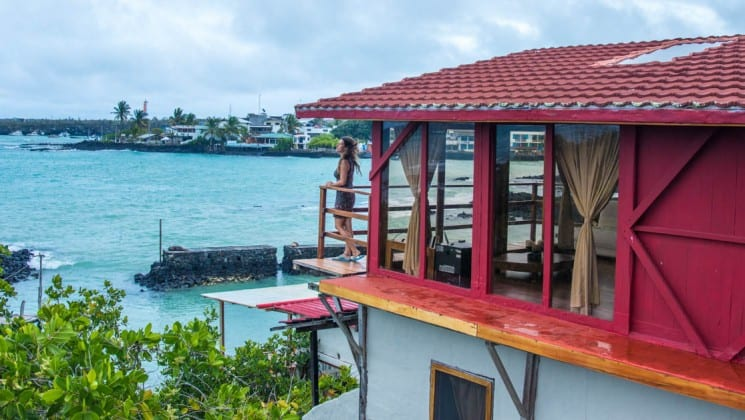 Woman stands on balcony outside her oceanfront suite at Galapagos Habitat Eco Luxury Hotel on Santa Cruz in the Galapagos Islands