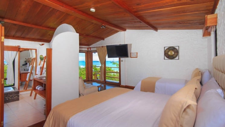Suite with two beds, chairs, TV, tub, balcony and ocean views at Galapagos Habitat Eco Luxury Hotel on the Galapagos Island of Santa Cruz