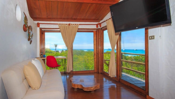 Couch, coffee table, TV, side table with stool, sliding door to balcony with ocean views at Galapagos Habitat Eco Luxury Hotel on the Galapagos Island of Santa Cruz