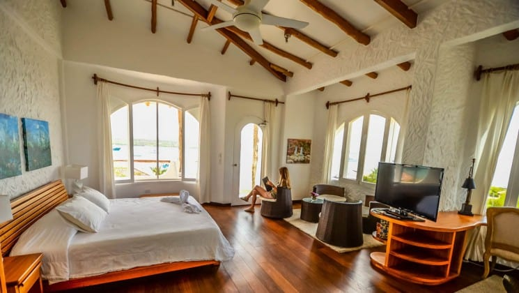 a large bed and a woman reading in a chair next to it in an open room in the Angermeyer Waterfront Inn galapagos hotel