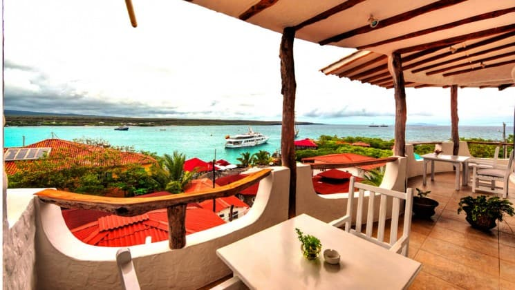 a table and chairs sitting on the balcony of the Angermeyer Waterfront Inn galapagos hotel with the ocean and a small ship in the background