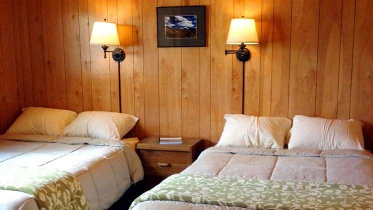Two double beds with small table and two wall lamps at Denali Education Center near Denali National Park in Alaska