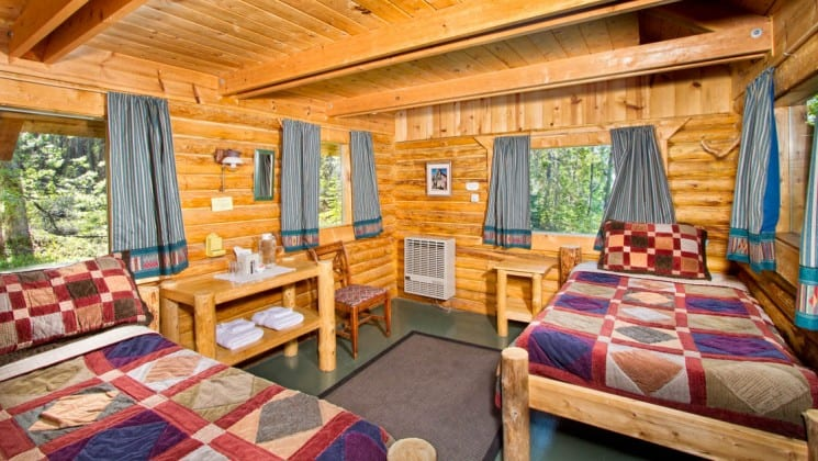 A private guest cabin at the Kenai Backcountry Lodge in Alaska features heated interiors, two beds, simple furnishings, a private porch and propane light.