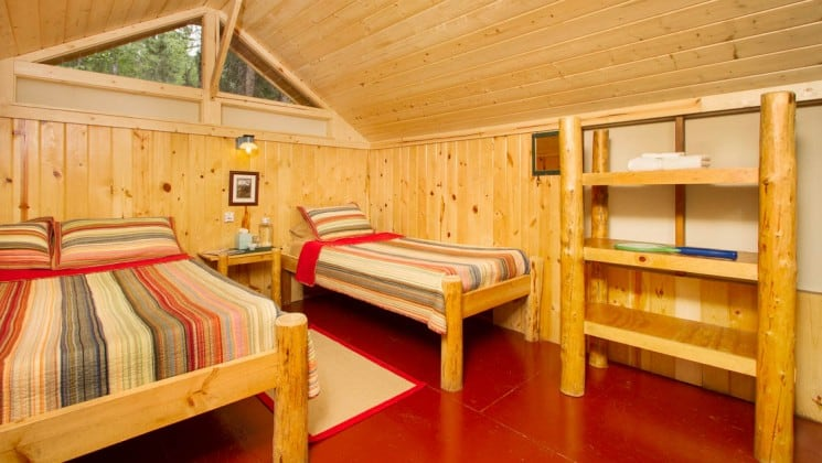 Inside a private guest cabin with two beds and simple furnishings and a propane light at the Kenai Backcountry Lodge in Alaska