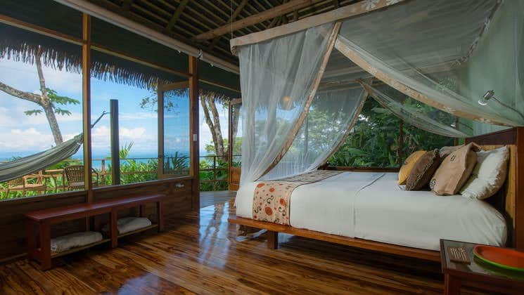 A room with a king-sized bed, balcony, hammock, and oceanview at Lapa Rios Eco Lodge, in Costa Rica's Oso Peninsula