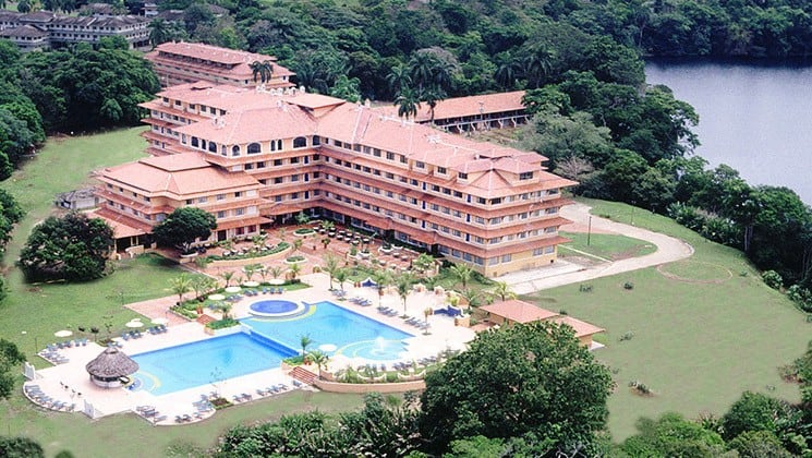 An aerial view of the Meliá Panamá Canal, a large hotel with a swimming pool near lush rainforest and Gatun Lake