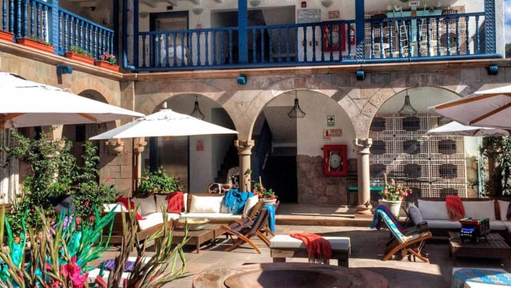 Sunny, open air courtyard with lounges, shade umbrellas, plants and stairs to upper level at El Mercado Tunqui in Cusco, Peru