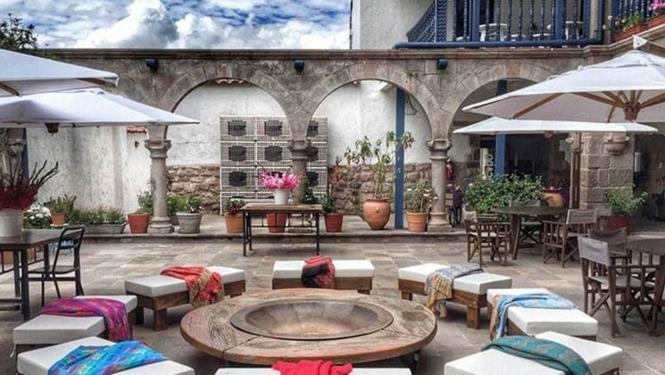 Sunny outdoor courtyard with benches surrounding a firepit at El Mercado Tunqui in Cusco, Peru