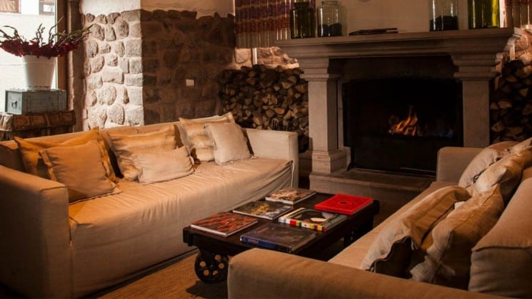 Two couches, a coffee table, and a wood fireplace in the lounge at El Mercado Tunqui in Cusco, Peru