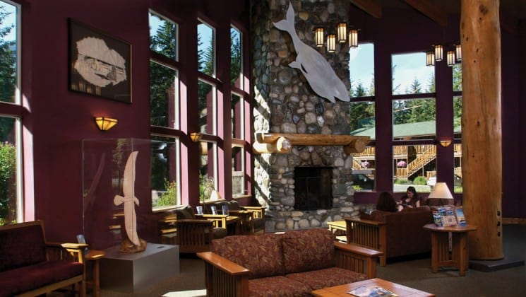 Light streams through large windows facing the mountain range. The main lodge at the Seward Windsong Lodge in Alaska offers an espresso bar with snacks, couches and a stone fireplace.